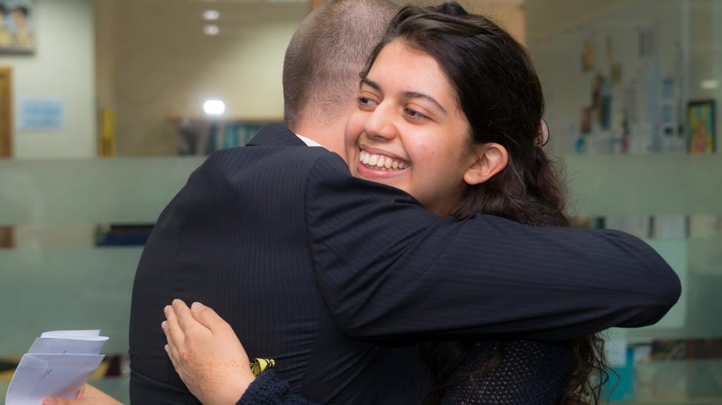 Sara Dube of Jumeirah English Speaking School hugs Ian Thurston, the deputy head of KS5 at JESS. Sara scored a perfect 45 in her IB test results. Navin Khianey for The National