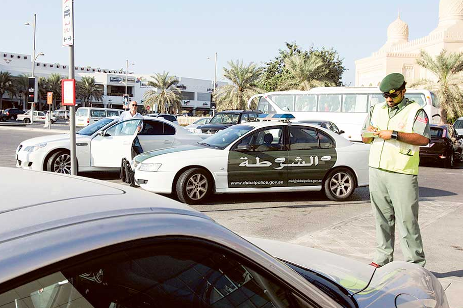 A policeman fines a car outside the Jumeirah Mosque. Image Credit:Gulf News Archive